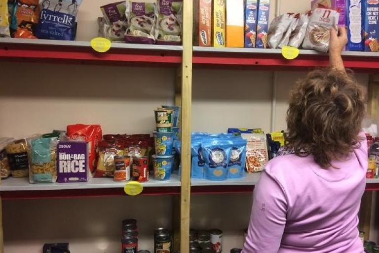 A woman browsing shelves of food at a food stop